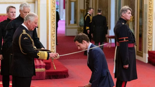 Andy Murray kneels as he receives his knighthood from Prince Charles