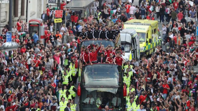 Fans cheer as they line Westgate Street to welcome the Wales team home
