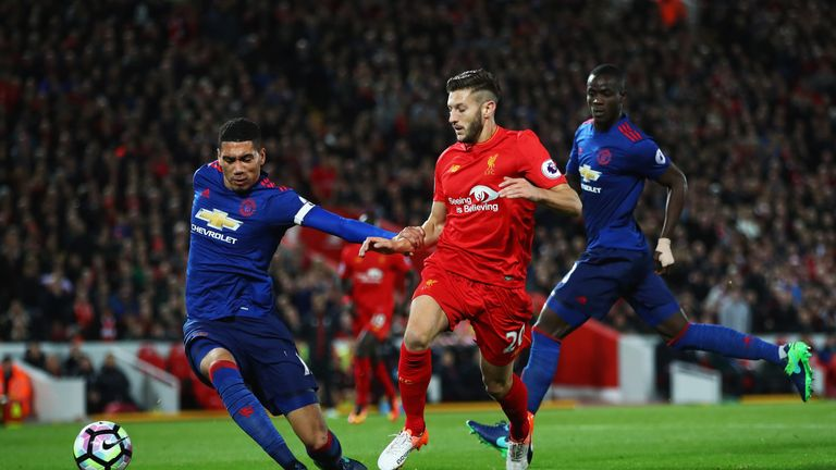 Chris Smalling and Eric Bailly challenge Adam Lallana at Anfield