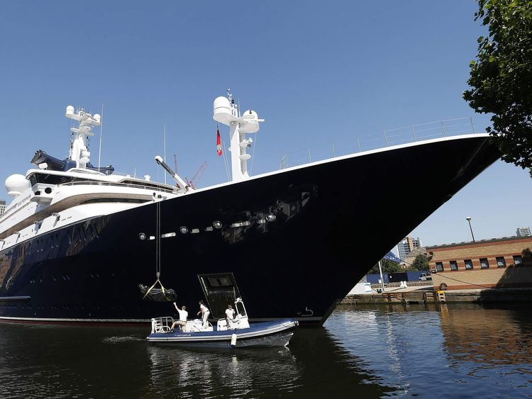 Crew works around Octopus, luxury yacht owned by Microsoft co-founder Paul Allen, moored at Canary Wharf, London