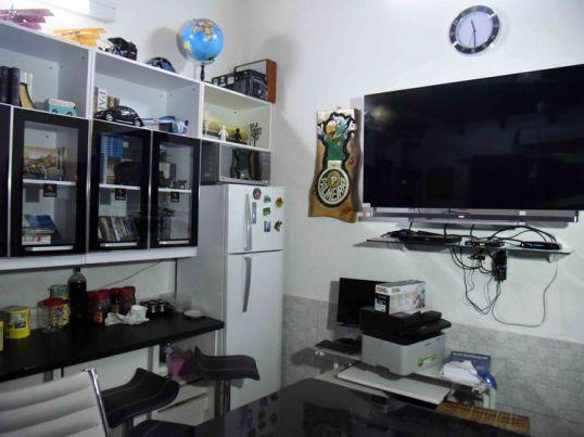 A plasma TV screen hangs on the wall alongside a fridge