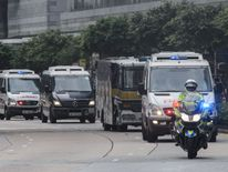 Police escort a prison van with Rurik Jutting on board to the High Court in Hong Kong