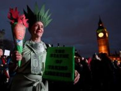 A demonstrator dressed as the Statue of Liberty takes part in a protest against Mr Trump