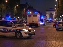 Police vehicles line the Champs-Elysees in Paris following a shooting incident