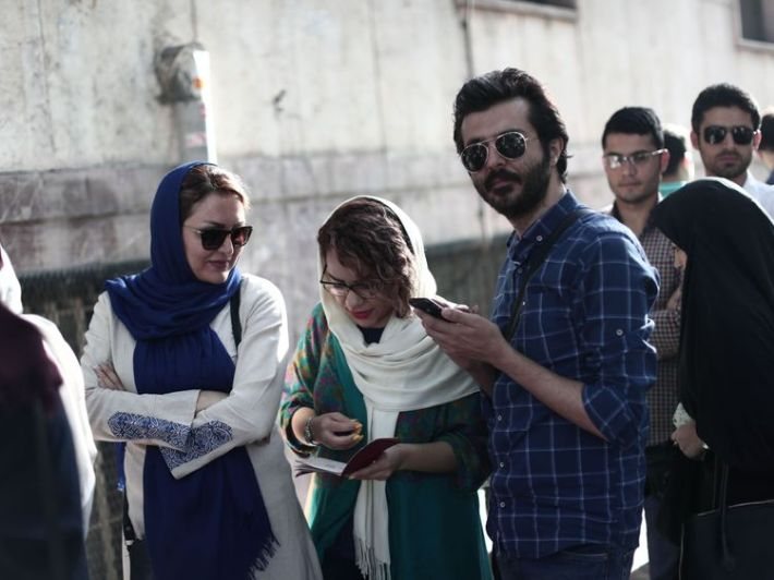 Iranians wait in a queue for the opening of the polling station to cast their ballots for the presidential elections in Tehran on May 19, 2017