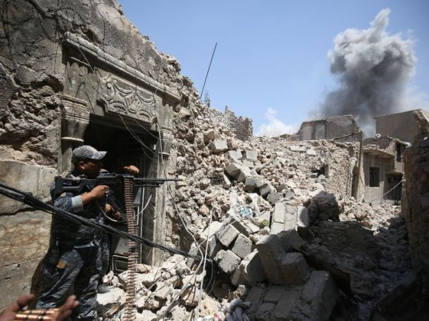 Members of the Iraqi federal police hold position during an armed exchange while advancing through the Old City of Mosul