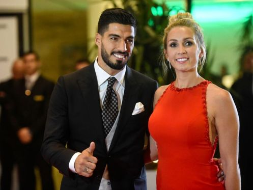 Uruguayan football player Luis Suarez and his wife Sofia Balbi pose on a red carpet during Barcelona's football star Lionel Messi and Antonella Roccuzzo wedding
