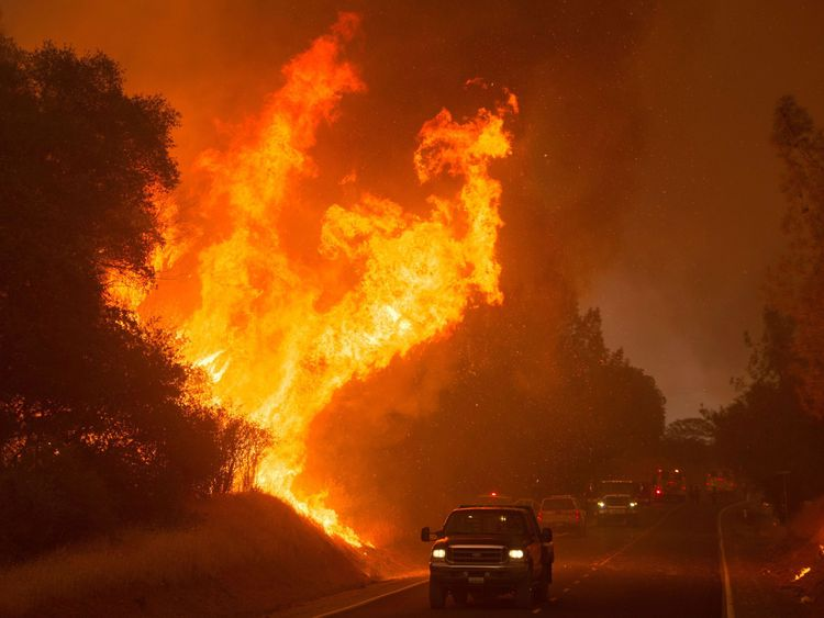 Motorists drive past the flames