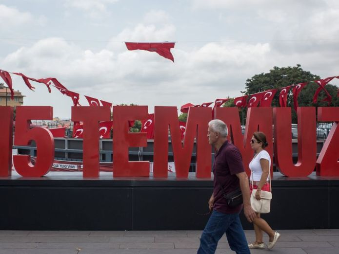 STANBUL, TURKEY - JULY 14: People are seen walking past a anniversary site setup to honour the victims of the July 15, 2016 coup attempt a day ahead of the first anniversary of the failed coup attempt on July 14, 2017 in Istanbul, Turkey. July 15, 2017 will mark the first anniversary of the failed coup attempt which saw 249 people die when military personnel attempted to over throw the government and President Recep Tayyip Erdogan. Extensive commemorations have been planned for the July 15 anniv