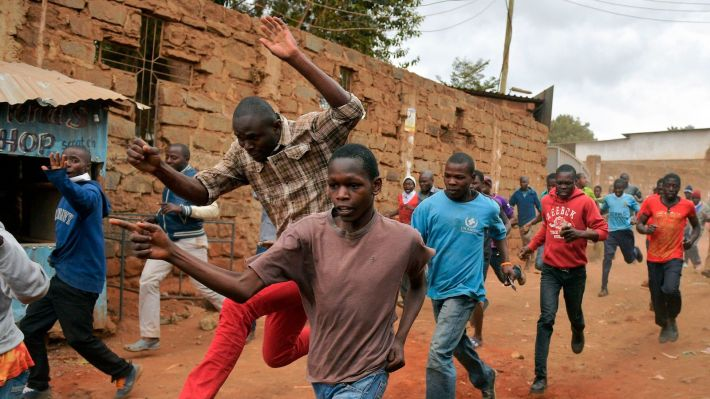 Protesters run away after riot police fired live rounds in the Kibera slum in Nairobi