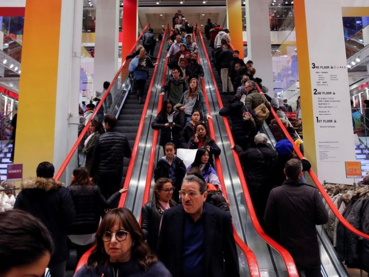 Shoppers ride escalators during Black Friday sales at the Uniqlo Fifth Avenue store in Manhattan, New York, U.S., November 25, 2016. REUTERS/Andrew Kelly