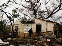 A man looks for valuables in the damaged house of a relative in Guayama, Puerto Rico
