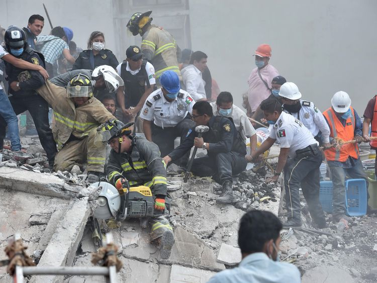 Rescuers, firefighters, policemen, soldiers and volunteers remove rubble and debris from a flattened building in search of survivors after a powerful quake in Mexico City on September 19, 2017