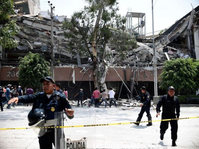 Police try to clear the area around a collapsed building in Mexico City