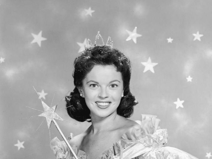 1958: American actor Shirley Temple wears a fairy godmother costume, which includes a magic wand and a tiara, in a promotional portrait for her television series of dramatized fairy tales, 'Shirley Temple's Storybook'. (Photo by Hulton Archive/Getty Images)