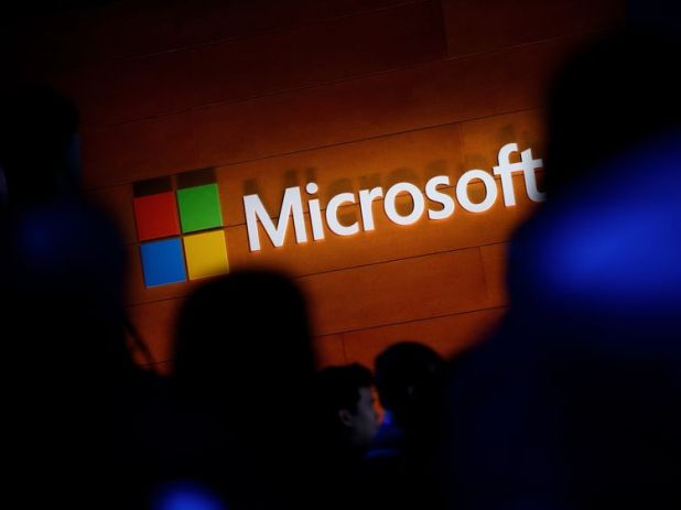 The Microsoft logo is illuminated on a wall during a Microsoft launch event to introduce the new Microsoft Surface laptop and Windows 10 S operating system, May 2, 2017 in New York City