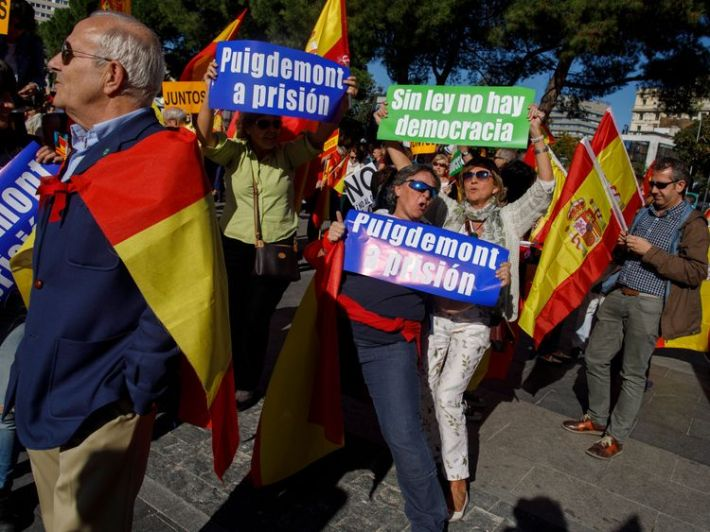 Demonstrators' placards read 'Puigdemont to prison' (L) and 'No law, no democracy' (R)