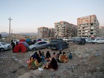 Residents huddle by a fire in an open area following a 7.3-magnitude earthquake at Sarpol-e Zahab in Iran's Kermanshah province