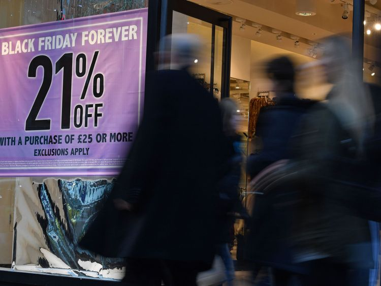 Shoppers pass a promotional sign for Black Friday sales discounts on Oxford Street