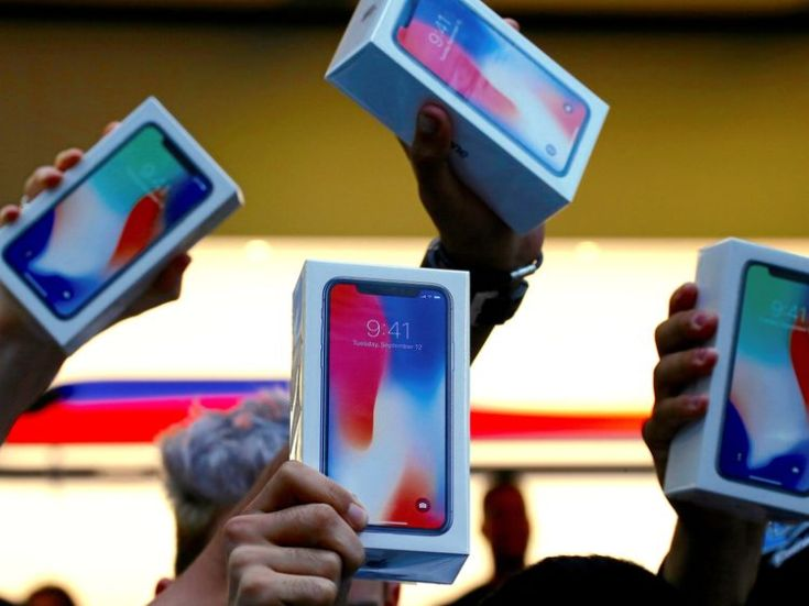 Customers hold up newly purchased iPhone Xs outside the Apple store in Sydney
