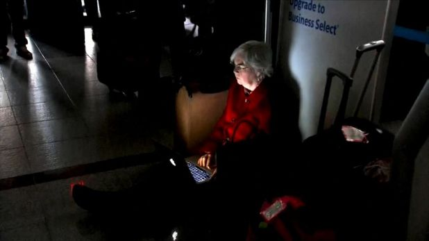 A woman uses te light of her laptop during the Atlanta Airport power outage