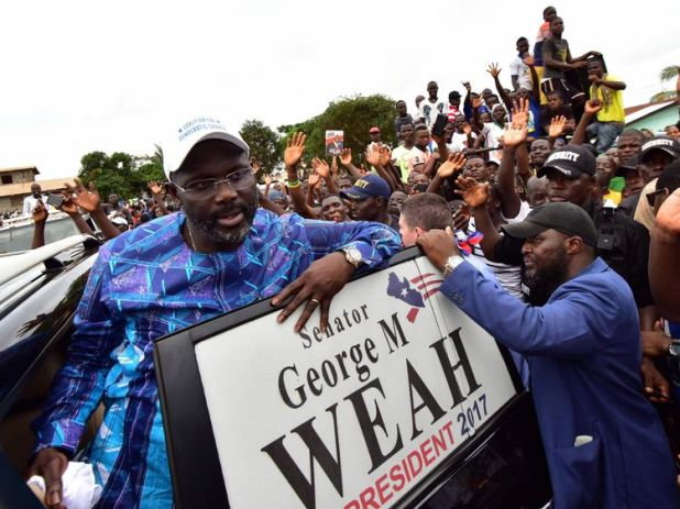 Former international Liberian football star turned politician George Weah, greets supporters during a campaign rally in Monrovia on October 8, 2017, three days ahead of the country's elections. Liberians go to the polls on October 10, to pick their first new president in 12 years as Ellen Johnson Sirleaf closes the page on two terms dominated by post-war reconstruction and the Ebola crisis. / AFP PHOTO / ISSOUF SANOGO (Photo credit should read ISSOUF SANOGO/AFP/Getty Images)