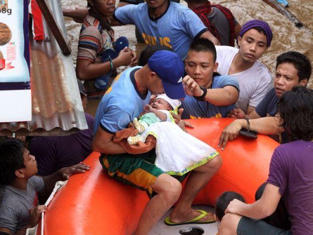 Policemen evacuate a baby in Cagayan City