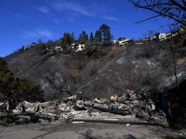 burnt out house is seen after the Skirball wildfire swept through the exclusive enclave of Bel Air, California on December 7, 2017. Local emergency officials warned of powerful winds on December 7 that will feed wildfires raging in Los Angeles, threatening multi-million dollar mansions with blazes that have already forced more than 200,000 people to flee. / AFP PHOTO / MARK RALSTON (Photo credit should read MARK RALSTON/AFP/Getty Images) Editorial subscription SML 4712 x 3296 px | 39.89 x 27.91