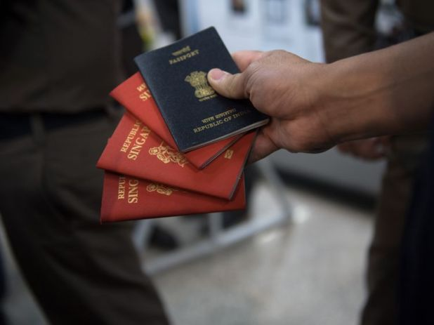 A Thai immigration officer displays some of the fake passports