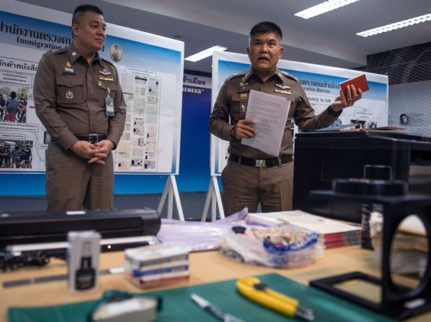The immigration chief holds up a fake passport during the news conference