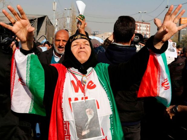 A woman wears a portrait of Supreme leader Ayatollah Ali Khamenei during a pro-government march in Iran