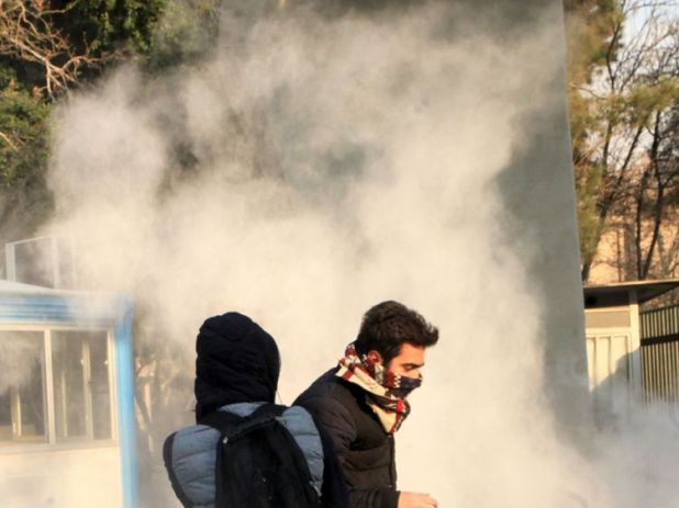 Students run for cover from tear gas during protests at the University of Tehran
