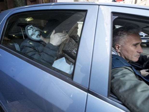 Italian Police escort Carmine Spada (L on backseat), the chief of the clan, during an anti-mafia operation against the Spada clan in Ostia, near Rome, Italy