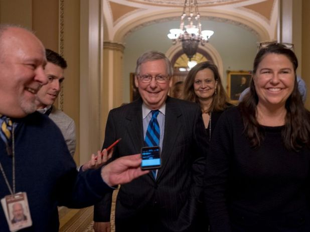 Mitch McConnell (centre) could not stop the shutdown entering a new week
