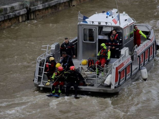 Members of the Paris Fire Brigade help in the search for a missing police diver