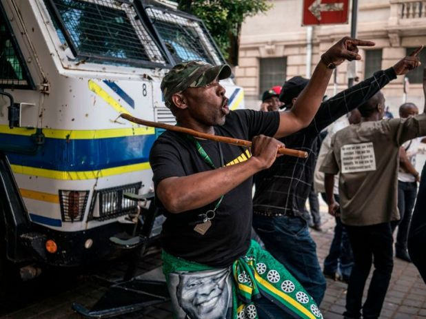 Supporters of the ANC Deputy President Cyril Ramaphosa dance and chant slogans during a demonstration outside the ANC party headquarter in Johannesburg