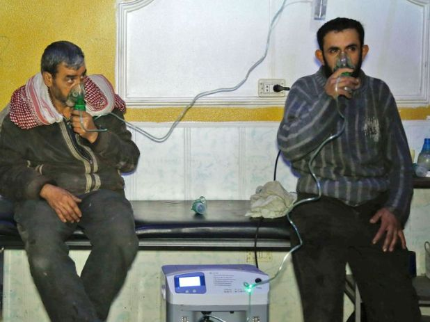 Syrian men wear oxygen masks following a reported gas attack on the rebel-held besieged town of Douma