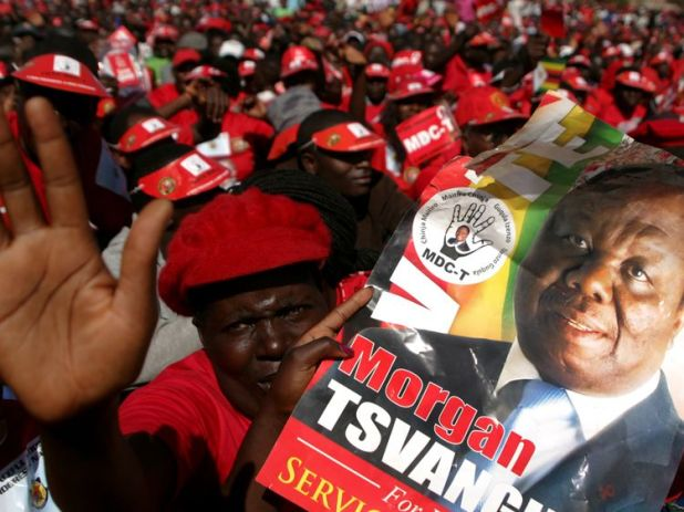Supporters of the Movement for Democratic Change presidential candidate Morgan Tsvangirai holds his portrait as they attend the final campaign rally 'Cross Over' on July 29, 2013 at the 'Freedom Square' in Harare ahead of the general elections held on July 31, 2013. Zimbabweans vote for a new president and parliament on July 31 , four years after Zimbabwe's President Robert Mugabe-- who has ruled for 33 years -- and Prime Minister Morgan Tsvangirai were forced to share power. AFP PHOTO / JEKESAI