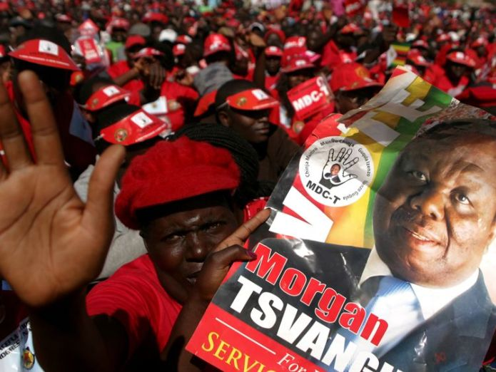 Supporters of the Movement for Democratic Change presidential candidate Morgan Tsvangirai holds his portrait as they attend the final campaign rally 'Cross Over' on July 29, 2013 at the 'Freedom Square' in Harare ahead of the general elections held on July 31, 2013. Zimbabweans vote for a new president and parliament on July 31 , four years after Zimbabwe's President Robert Mugabe-- who has ruled for 33 years -- and Prime Minister Morgan Tsvangirai were forced to share power. AFP PHOTO / JEKESAI Zimbabwe opposition leader Tsvangirai dies Zimbabwe opposition leader Tsvangirai dies skynews zimbabwe tsvangirai 4231258