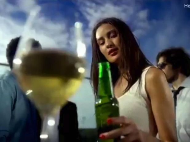 The bottle is passed to a light-skinned woman. Pic: Heineken