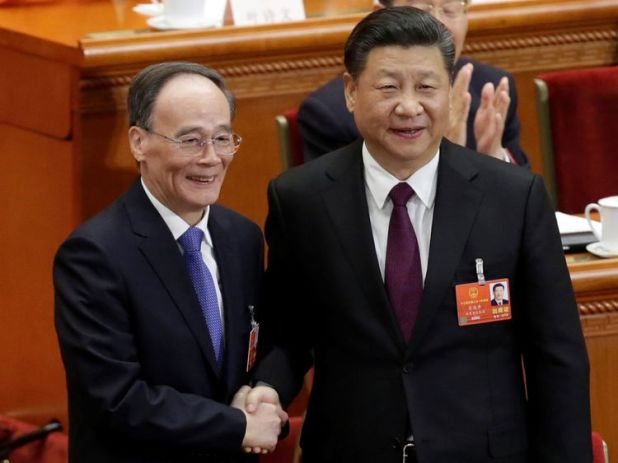 Chinese President Xi Jinping (R) shakes hands with newly elected Chinese Vice President Wang Qishan at the fifth plenary session of the National People's Congress (NPC) at the Great Hall of the People in Beijing, China March 17, 2018. REUTERS/Jason Lee