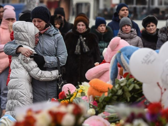 People grieve at a makeshift memorial in Kemerovo