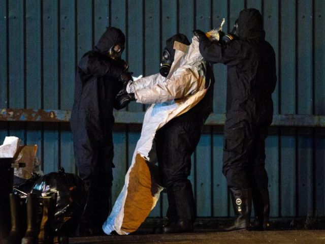 Police officers remove their protective suits on an industrial site as they continue investigations into the poisoning of Sergei Skripal