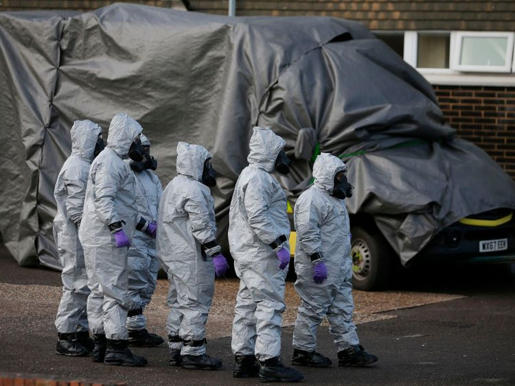 Personnel in protective coveralls and breathing equiptment cover an ambulance with a tarpaulin at the Salisbury District Hospital in Salisbury, southern England, on March 10, 2018