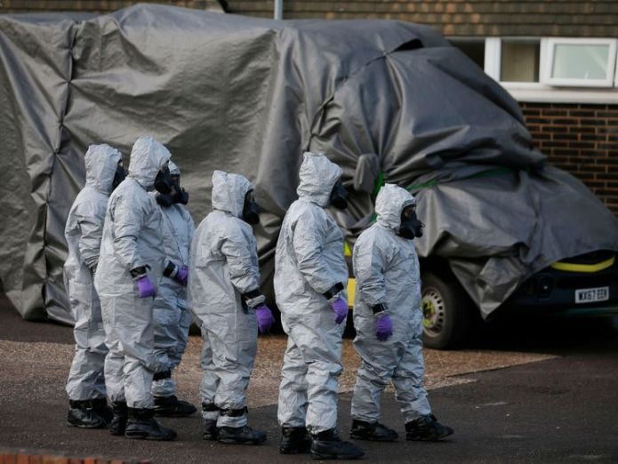 Personnel in protective coveralls and breathing equiptment cover an ambulance with a tarpaulin at the Salisbury District Hospital in Salisbury, southern England, on March 10, 2018  US imposes sanctions on Russia over Skripal poisonings in Salisbury skynews skripal salisbury ambulance 4252021