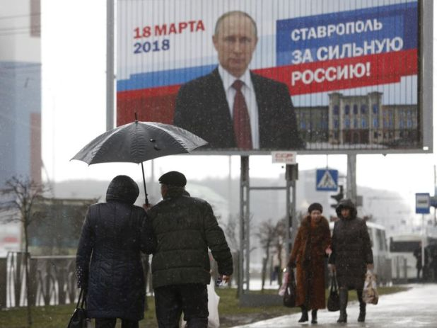"People walk next to the election campaign poster of Russian President Vladimir Putin in Stavropol, Russia March 14, 2018. The board reads ""Stavropol is for strong Russia!"" REUTERS/Eduard Korniyenko"