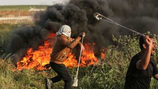 Palestinian protesters use slingshots to throw stones during clashes with Israeli forces A portrait of grief after day of deadly violence A portrait of grief after day of deadly violence skynews gaza israel 4274488
