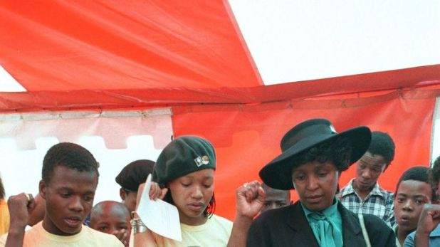 JOHANNESBURG, SOUTH AFRICA: Photo dated 24 January 1987 shows Winnie Madikizela-Mandela (R, with hat) with her daughter Zinzi (2nd L) and members of the Mandela Football Club singing political slogans in Soweto at the funeral of one of the team members killed in political clashes. Madikizela-Mandela will appear at the Truth and Reconcilliation Commission (TRC) hearing to testify on allegations of her involvement in the deaths of young political activists although a key witness, Katiza Cebekhulu,
