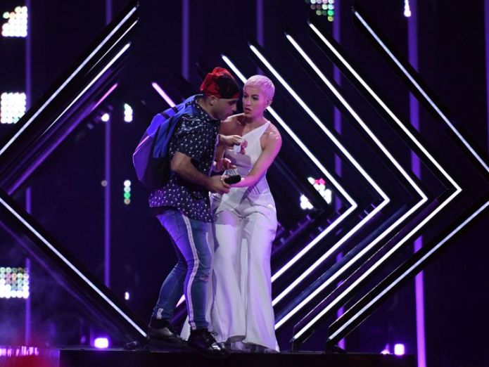 A man takes the microphone from Britain's singer Susanna Marie Cork aka SuRie as she performs 'Storm' during the final of the 63rd edition of the Eurovision Song Contest 2018 at the Altice Arena in Lisbon, on May 12, 2018. (Photo by Francisco LEONG / AFP) (Photo credit should read FRANCISCO LEONG/AFP/Getty Images) Stage invader grabs mic during UK Eurovision performance Stage invader grabs mic during UK Eurovision performance skynews eurovision song contest 4308300