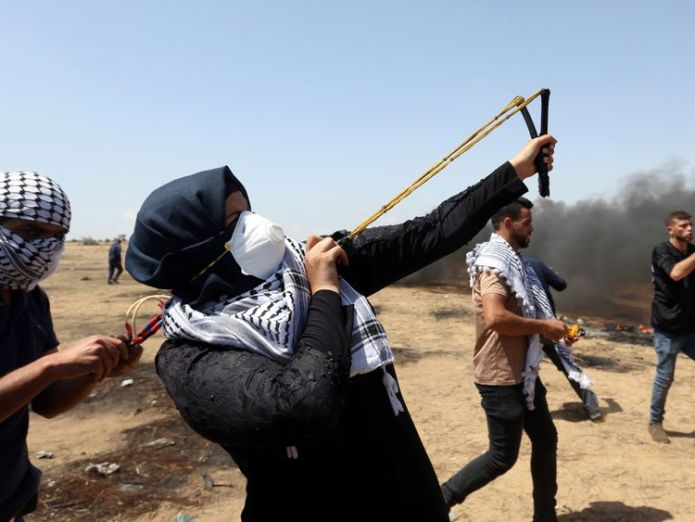 A female demonstrator uses a slingshot to hurl stones at Israeli forces  Palestinians shot dead as 'volatile' Gaza border protest intensifies Palestinians shot dead as 'volatile' Gaza border protest intensifies skynews gaza palestinian protests 4306746